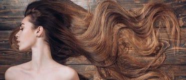 Kobieta z piękny długie włosy na drewnianym tle długie włosy Modni ostrzyżenia Piękno włosiany salon zdjęcia royalty free