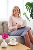 Kobieta z pięknym uśmiechu writing listem podczas gdy siedzący na sof Zdjęcia Royalty Free
