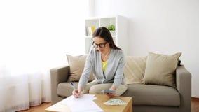 Kobieta z pieniądze, papierami i kalkulatorem, w domu zbiory wideo