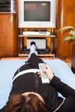 Kobieta z pilot do tv dopatrywaniem TV Zdjęcie Royalty Free