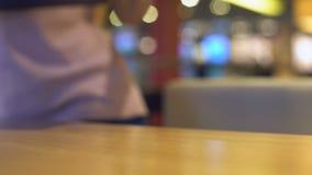 Kobieta z plastikowym tacy obsiadaniem przy kawiarnia stołem, samoobsługowa restauracja, bakłaszka zdjęcie wideo
