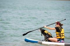 Kobieta z psem na paddle desce zdjęcie royalty free