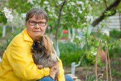 Kobieta z psim Pekingese w wiosna ogródzie fotografia stock