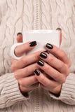 Kobieta z pulowerem trzyma filiżankę herbata w rękach z czarnym nai Zdjęcie Stock