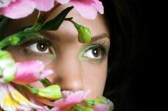 Kobieta z różowymi kwiatami. Ostrość na oczach zdjęcia royalty free