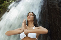 Kobieta Z rękami Spinał spełniania joga Przeciw siklawie Zdjęcia Royalty Free