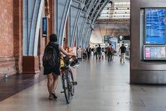 Kobieta z roweru odprowadzeniem wśrodku St Pancras staci, Londyn, UK obrazy royalty free