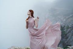 Kobieta z rozwija suknią na falezy twarzy, mgłowa pogoda Fotografia Stock
