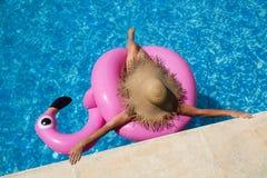Kobieta z słomianym kapeluszem w basenie z nadmuchiwanym różowym flamingiem zdjęcie royalty free