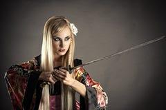 Kobieta z samuraja kordzikiem na szarość Zdjęcia Royalty Free