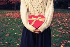Kobieta z serce kształtującym pudełkiem w parku Fotografia Royalty Free