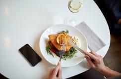 Kobieta z smartphone łasowania sałatką przy restauracją Obrazy Royalty Free