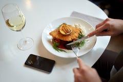 Kobieta z smartphone łasowania sałatką przy restauracją Zdjęcie Stock