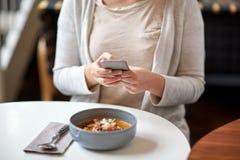 Kobieta z smartphone i bani polewką przy kawiarnią Zdjęcia Royalty Free