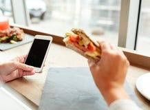 Kobieta z smartphone i kanapką przy restauracją Obrazy Royalty Free