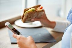 Kobieta z smartphone i kanapką przy restauracją Zdjęcia Stock