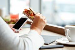 Kobieta z smartphone i kanapką przy restauracją Zdjęcia Royalty Free