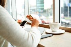 Kobieta z smartphone i kanapką przy restauracją Fotografia Stock