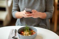 Kobieta z smartphone i pucharem polewka przy kawiarnią Zdjęcia Stock