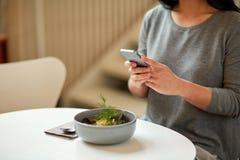 Kobieta z smartphone i pucharem polewka przy kawiarnią Zdjęcie Stock