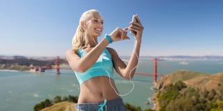 Kobieta z smartphone i słuchawkami robi sportom Obraz Royalty Free