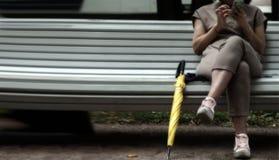Kobieta z smartphone obsiadaniem na ławce w parku z parasolem Zdjęcie Stock