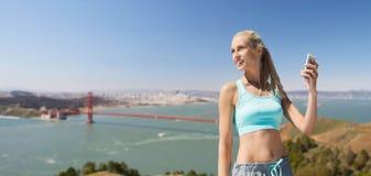 Kobieta z smartphone robi sportom nad mostem Fotografia Stock