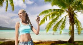 Kobieta z smartphone robi sportom nad plażą Obrazy Stock