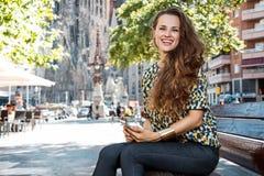 Kobieta z smartphone siedzi na ławce nie daleko od Sagrada Familia Obrazy Royalty Free