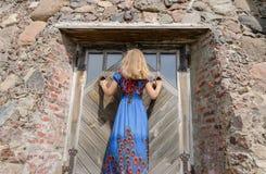 Kobieta z suknią przy retro starym rezydenci ziemskiej drzwi wejściem obrazy royalty free