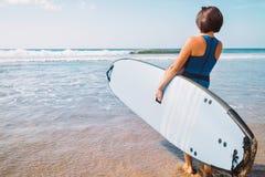 Kobieta z surfboard pobytem na ocean plaży zdjęcie stock