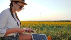 Kobieta z telefonem komórkowym i baterią, dziewczyna używa wiszącą ozdobę i panelu słonecznego komunikuje w ogólnospołecznej siec zbiory wideo