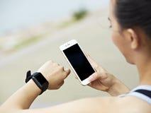 Kobieta z telefonem komórkowym i sprawność fizyczna tropicielem Obraz Stock