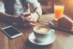 Kobieta z telefonem komórkowym na stole, texting w ogólnospołecznych środkach, śniadanie przystojna biznesowa dama Zdjęcie Royalty Free