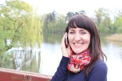 Kobieta z telefonem komórkowym w parku Zdjęcia Stock