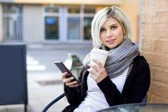 Kobieta Z telefonem komórkowym I filiżanką Przy chodniczek kawiarnią Zdjęcie Stock