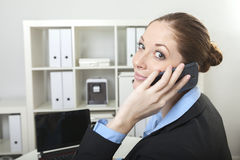 Kobieta z telefonem przy jej biurkiem Zdjęcia Stock
