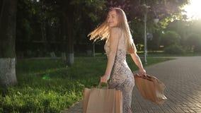 Kobieta z torba na zakupy przędzalnianymi w parku wokoło zdjęcie wideo