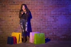 Kobieta z torba na zakupy Używać telefon komórkowego Przeciw ściana z cegieł Obrazy Royalty Free