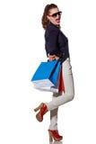 Kobieta z torba na zakupy w okularach przeciwsłonecznych ma zabawa czas na bielu Zdjęcie Stock