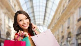 Kobieta z torbami na zakupy nad centrum handlowego tłem fotografia royalty free