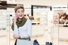 Kobieta z torbami na zakupy, używać mądrze telefon podczas zakupy w centrum handlowym zdjęcia stock