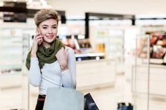 Kobieta z torbami na zakupy, używać mądrze telefon podczas zakupy w centrum handlowym obraz royalty free