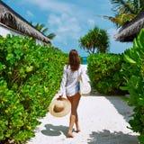Kobieta z torby i słońca kapeluszem iść wyrzucać na brzeg Fotografia Stock