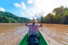 Kobieta z tradycyjnym kapeluszem p?ywa statkiem na br?z wodzie Nam Ou rzeka w Laos, zadziwiaj?ca krajobrazowa halna d?ungla s?awn zdjęcie royalty free