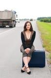 Kobieta z walizką na drodze Obraz Royalty Free