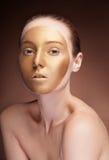 Kobieta z złocistą twarzą uzupełniał modę na brązie Zdjęcia Stock
