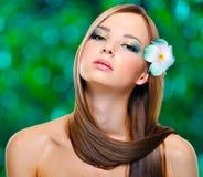 Kobieta z zdrowymi długimi hairs i kwiatami Zdjęcia Royalty Free