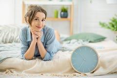 Kobieta z zegarem w sypialni zdjęcie stock