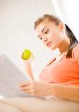 Kobieta z zieloną jabłczaną czytelniczą gazetą w domu Zdjęcia Royalty Free